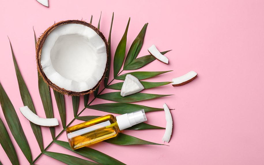 Flat lay image of a coconut and a bottle of coconut oil