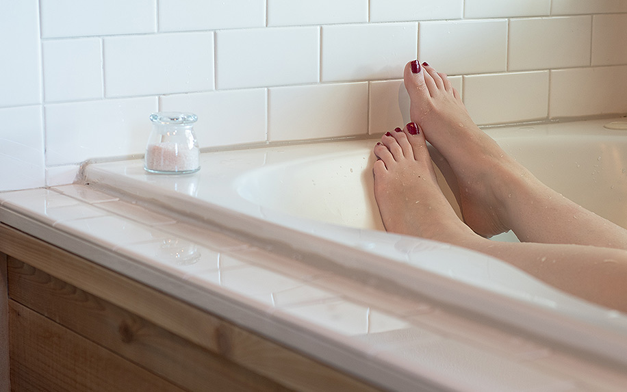 Womens feet crossed oover place at the bottom of a bath