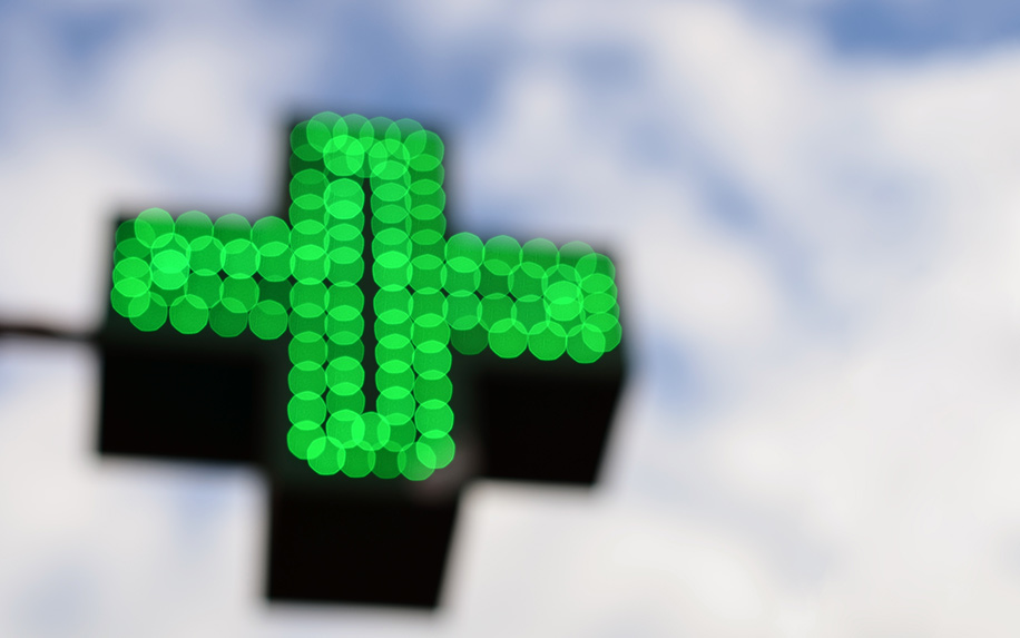 An image of the sky with a Pharmacy sign out of focus