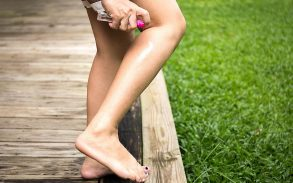 Woman spraying insect repellent on her leg in the garden