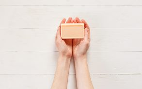 Top view of woman hands with solid soap on white wooden background