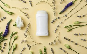 Flat lay composition with deodorant and herbs.
