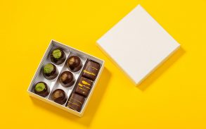 Assortment of luxury bonbons in box on bright yellow background.