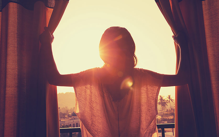 young woman stand in the room open curtain see sunrise